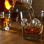 liquor barn forbes: bourbon being poured into a glass with ice cubes