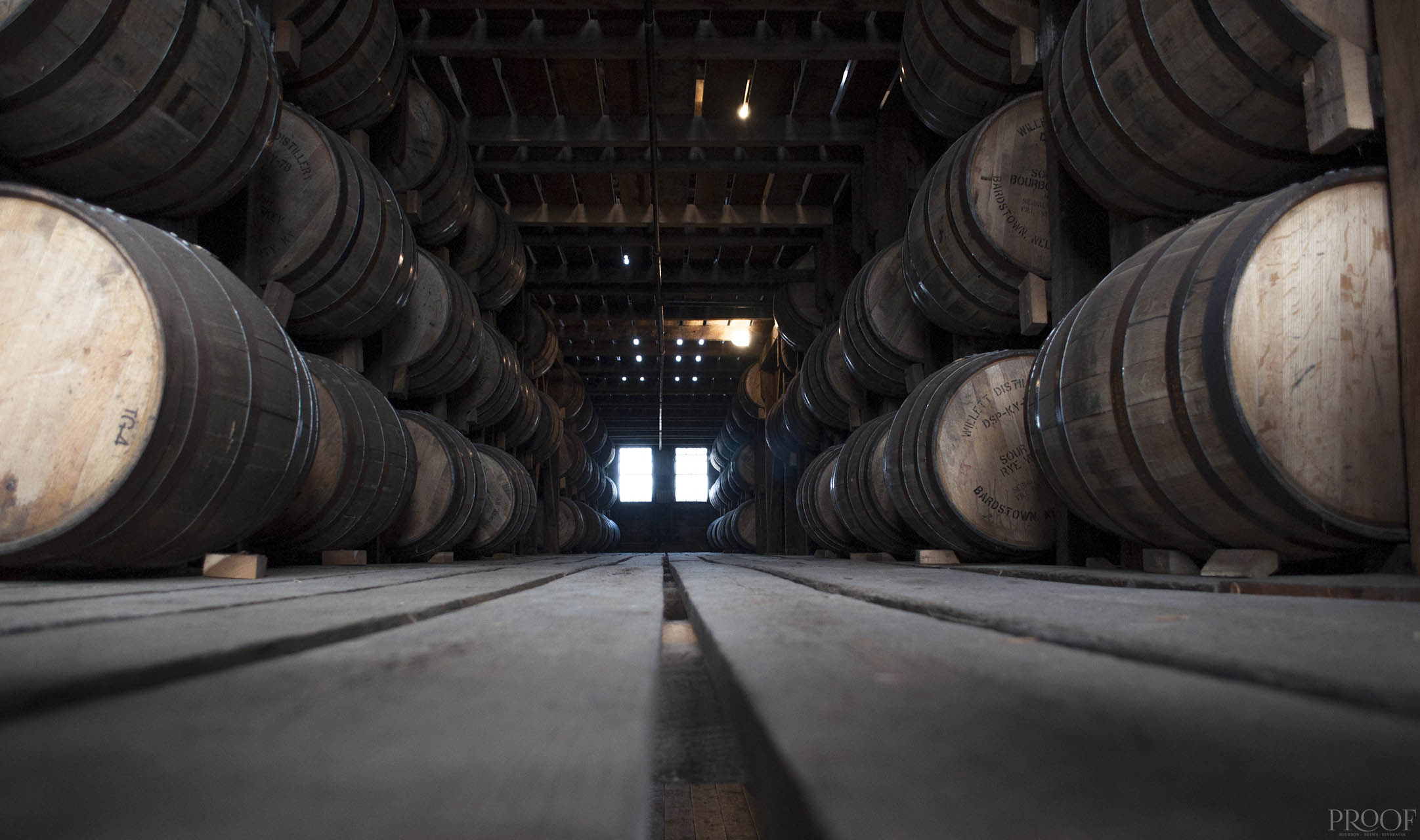 dark image of bourbon barrels stacked in a barn on both sides