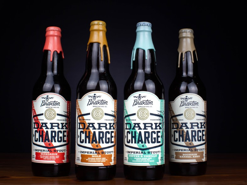 4 different style bottles of beer with a black background