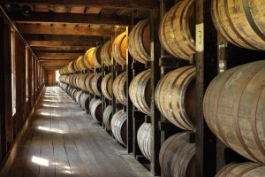 Cooperage: a long view of bourbon barrels stacked in a barn
