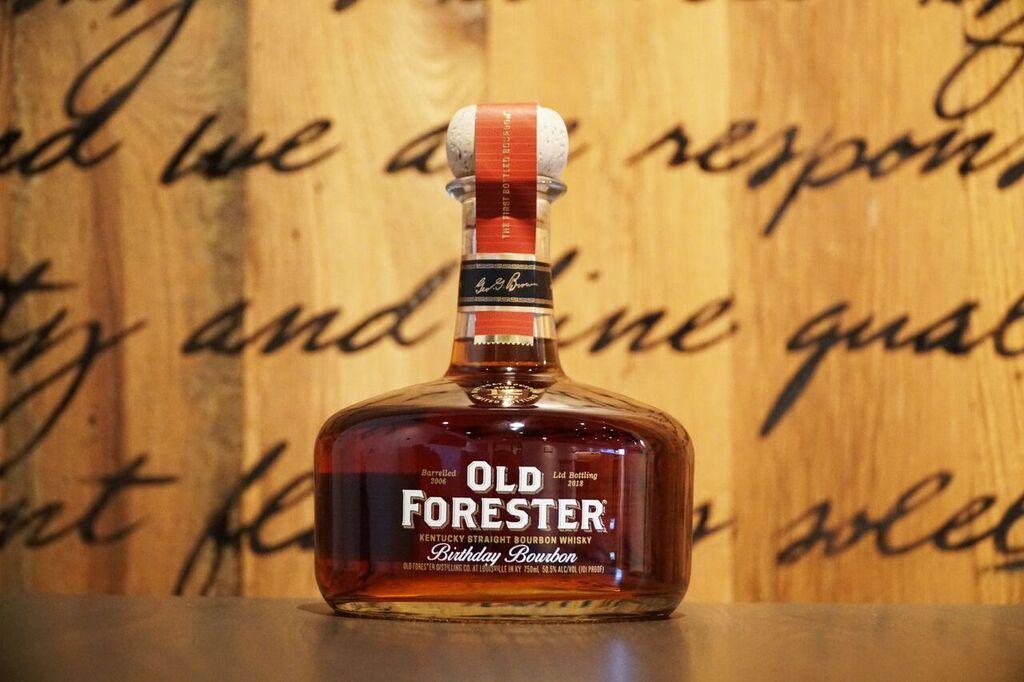 Medium color bourbon in heavy bottom glass bottle with bourbon barrel in background