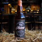 Mélange Brandy Barrel Aged Apple Ale sitting in straw
