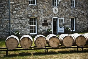 bourbon academy: rail with barrels on it in front of a stone building