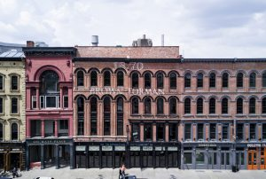 Brown-Forman: historic building that is a burnt orange that says 1870 brown-forman in white