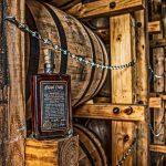 bottle of blood oath in front of a couple bourbon barrels