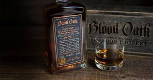 one bottle of blood oath with a glass of bourbon and blood oath sign in the background