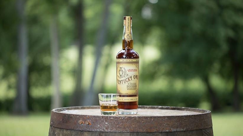 kentucky owl bottle with glass of bourbon on a barrel