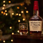 Maker's Mark bottle with glass of bourbon and blurry christmas lights in the background