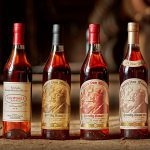 row of pappy van winkle bourbon bottles with a blurry background