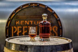 bottle and glass full of peerless bourbon