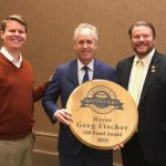 honored: mayor greg fischer holding a barrel head that says 100 proof award with 2 members of the KDA