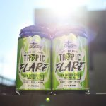 """two green cans outside with the sun in the background that say """"tropic flare"""""""