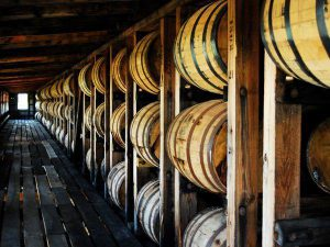 distillery: row of bourbon barrels in a wooden building