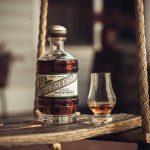 prohibition: a bottle of peerless and a glass with some bourbon on a wooden swing