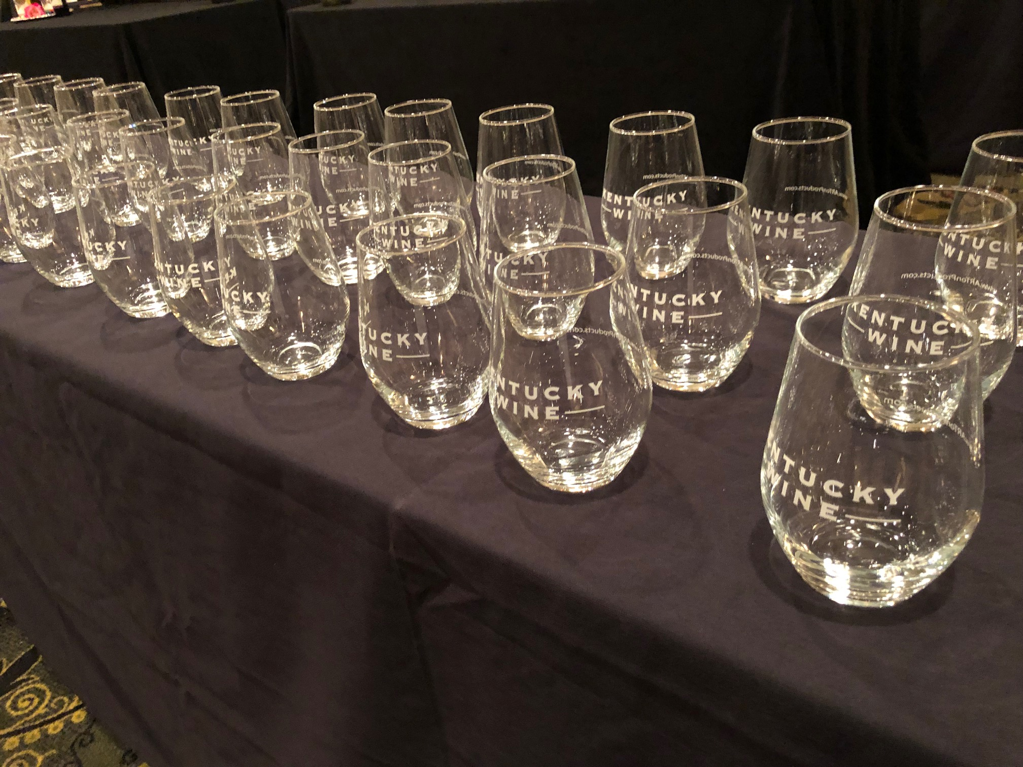 row of steamless wine glasses on a table with a black tablecloth