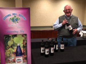 an older gentlemen holding a wine bottle with