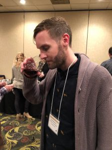 a man in a cardigan sniffing wine in a steamless wine glass