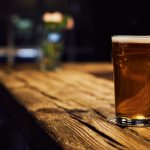 a single glass of craft beer on a wooden bar