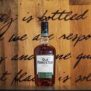 new old forester rye bottle in front of a bourbon barrel