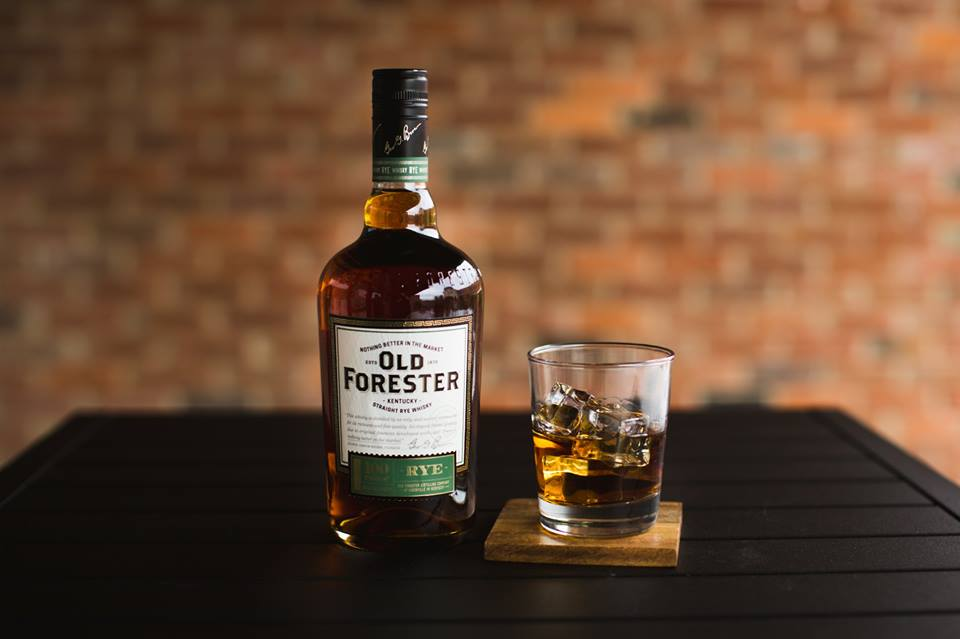 new old forester rye bourbon with a glass of bourbon on the rocks and a blurry brick background