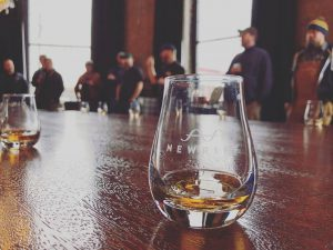 a small bourbon glass with a small amount of bourbon that says new riff barrels