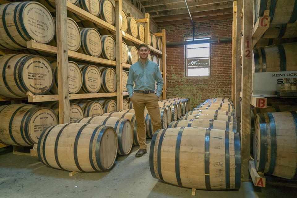 kentucky peerless: man in a blue button up and khaki pants standing between bourbon barrels