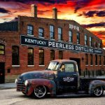 a brick building and an old fashioned truck with kentucky peerless on it and a blazing sun setting