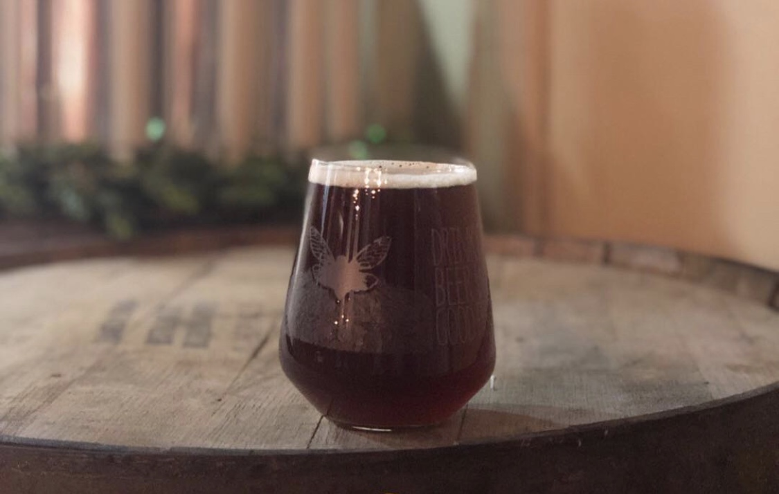somerset: glass of a dark beer on a barrel