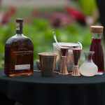 Kentucky Derby: woodford reserve bottle and cocktail tools on a table with a black table cloth