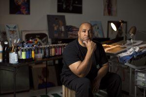 Kentucky Derby: a man in a black shirt sitting with an art studio behind him