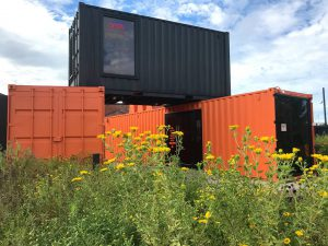 unique style: orange and black shipping containers with yellow flowers