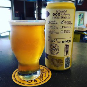 somerset: glass of light beer with a yellow can