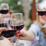 Women's History Month: group of people holding glasses filled with red wine