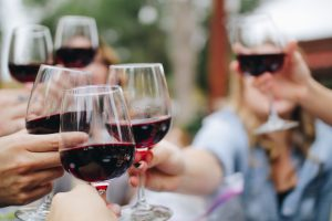 group of people holding glasses filled with red wine