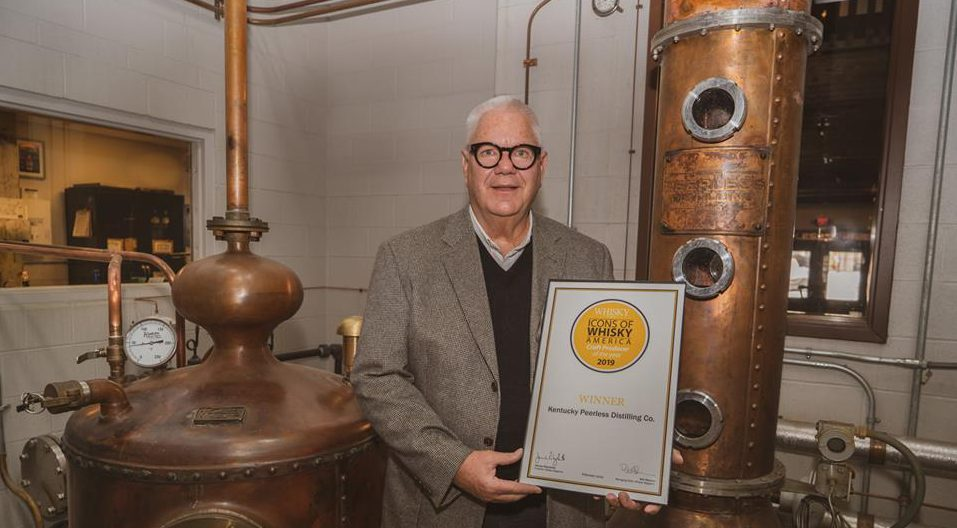 craft producer: man surrounded by bourbon equipment holding an award