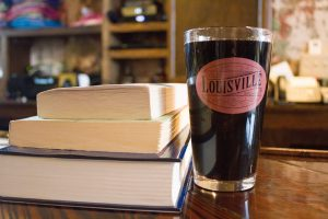 louisville brewer: dark beer in a class that says old louisville brewery next to books