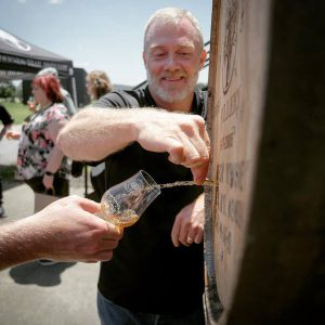 distillery: man pouring whiskey from a barrel