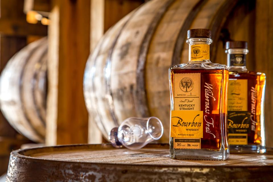 distillery: bottle of bourbon and a glass on a barrel and barrels in the background