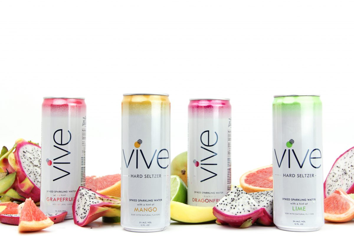 Hard Seltzer: four different skinny cans with different colors and fruit surrounding them