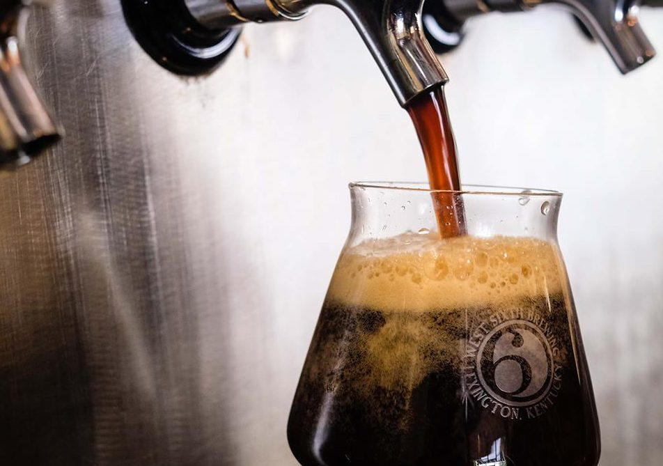 West Sixth: glass with west sixth logo having a dark beer poured into it