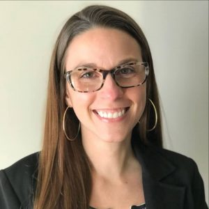 Bourbon Women: woman with glasses and a black blazer smiling at the camera