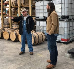 Moonshiners: two men standing in front of barrels talking