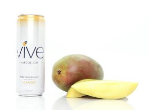 Hard Seltzer: white can with yellow on the top and a mango next to it