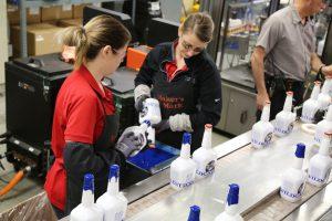 Maker's Mark: two women dipping white bottles in blue wax