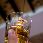 person holding a glass that says four roses
