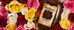 bottle of four roses in a bed of flowers