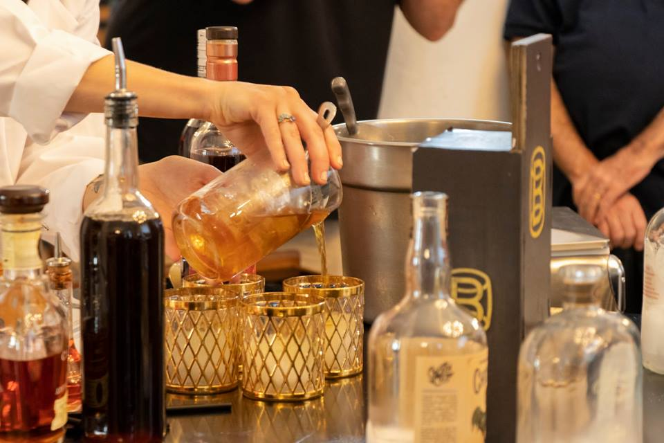 National Bourbon Day: a woman pouring bourbon in glasses