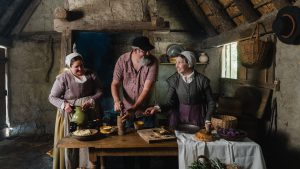 Beers: a man in modern clothing working with ingredients with two women in historic clothing