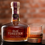 Old Forester: bottle of bourbon and a glass with bourbon and a brick wall in the background