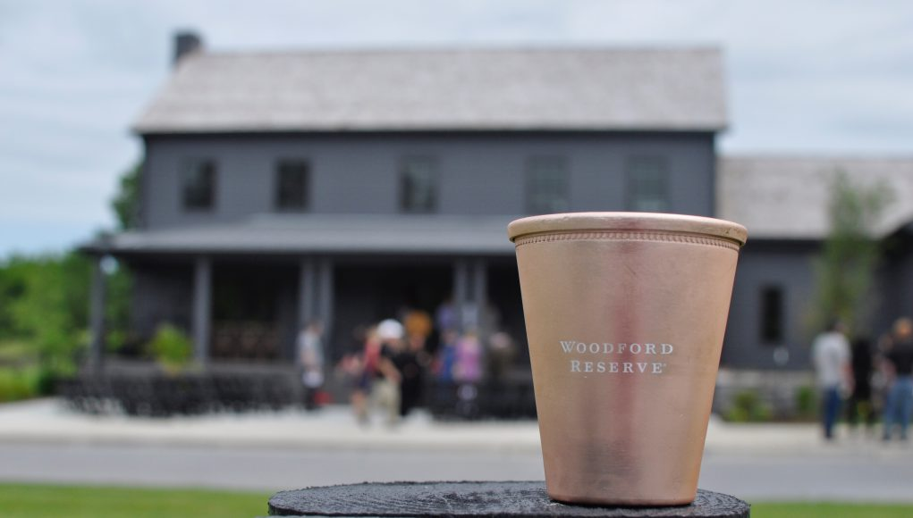 bourbon: a rose gold cup that says Woodford Reserve and a blurry building in the background